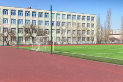Soccer football field near urban school. Building Royalty Free Stock Images