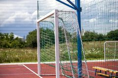 Soccer or football field playground with bright red soft rubber flooring, big gate, empty bench and protective net fence in rural stock photos