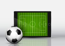 Soccer or football in front of an electronic device with pitch o. Soccer or football in front of an electronic device with grass pitch on screen Stock Photography