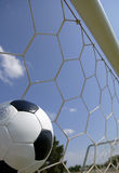 Soccer - Football in Goal. Soccer ball in goal with blue sky background royalty free stock photo