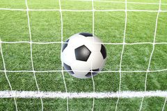 Soccer football in Goal net with green grass field. Stock Photos