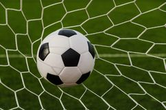 Soccer football in Goal net with green grass field. Image of Soccer football in Goal net with green grass field. For sport concept Stock Image