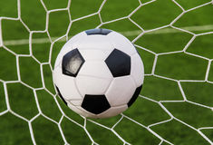 Soccer football in Goal net with green grass field. Royalty Free Stock Photo