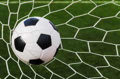 Soccer football in Goal net with green grass field. Royalty Free Stock Photography