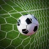 Soccer football in Goal net with green grass field. Royalty Free Stock Images