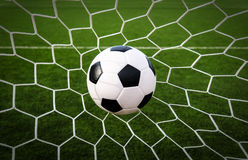 Soccer football in Goal net with green grass field. Stock Photography