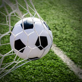 Soccer football in Goal net with green grass field. Stock Images