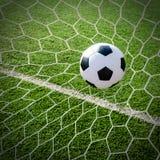 Soccer football in Goal net with green grass field. Stock Photos