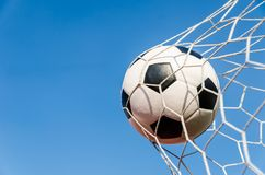 Soccer football in Goal net with the sky field. Stock Images