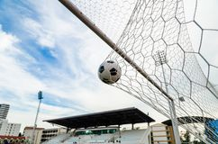 Soccer football in Goal net with the sky field. Stock Image