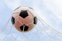 Soccer football in Goal net with the sky field. Stock Photo