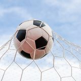 Soccer football in Goal net with the sky field. Royalty Free Stock Photo