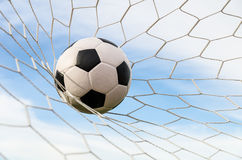 Soccer football in Goal net with the sky field. Stock Photography