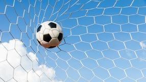 Soccer football in Goal net with the sky field. Stock Photos