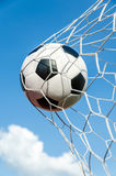 Soccer football in Goal net with the sky field. Royalty Free Stock Images