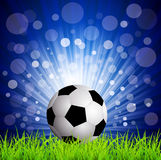 Soccer football on grass, on a blue background Royalty Free Stock Image