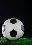 Soccer football on gree grass field with black bac Royalty Free Stock Image