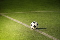 Soccer or Football on green field. With light beam Stock Photos