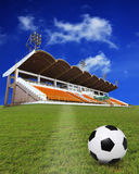 Soccer football on green field with stadium background Stock Photo