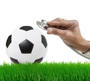 Soccer football on green grass field with hand and Stock Photos