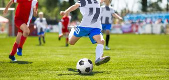 Soccer Football Kick. Young Player Kicking Soccer Ball. Footballers Running the Ball. Youth Soccer Tournament Competition Royalty Free Stock Photos