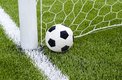 The soccer football with the net on the artificial green grass soccer field Stock Photos