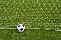 The soccer football with the net on the artificial green grass soccer field stock image