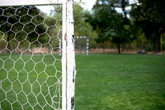 Soccer football net background over green grass and blurry stadium. Background of soccer football goal in stadium on match day Stock Photo