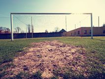 Soccer football net background over green grass and blurry stadium. Stock Images