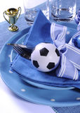 Soccer football party table in blue and white team colors - clos. Soccer football celebration party table setting with pates, cutlery, glasses, trophy, soccer Royalty Free Stock Photo