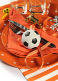 Soccer football party table in orange and white team colors - cl. Soccer football celebration party table setting with pates, cutlery, glasses, trophy, soccer Royalty Free Stock Photo