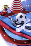 Soccer football party table in red white and blue team colors -. Soccer football celebration party table setting with pates, cutlery, glasses, trophy, soccer Stock Photography