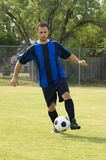 Soccer - Football Player dribbling. Soccer - Football Player Juggling in blue and black uniform royalty free stock photography