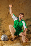 Soccer or football player screaming goal. Siiting on sand Stock Photos