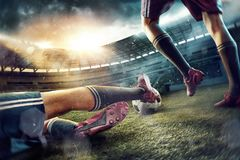 The soccer football players at the stadium in motion. The legs of soccer football players on green field of the stadium. Advertising concept of soccer football Stock Photos