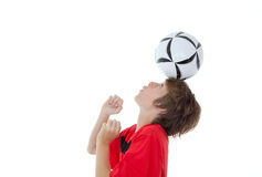 Soccer football skill. Young boy soccer or football player balancing ball on head royalty free stock photography