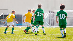 Soccer Football Teams Playing Soccer Football Match. Boys play soccer match. Yellow and green team on a sports field Royalty Free Stock Photo