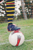 Soccer football under players boot. Ball under foot, soccer or football, with net on the field Stock Photography