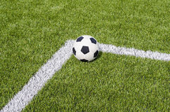 The soccer football on the white line in the artificial green grass field Stock Images