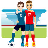 Soccer Friends And Rivals. Two soccer players friends and rivals of competing teams together on a soccer field Stock Photo