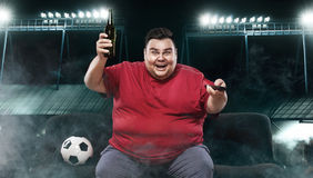 Soccer fun - happy and fat man watching football at the stadion, taking beer and soccer ball on yellow background. Royalty Free Stock Image