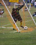 Soccer game action. Young man recovering soccer ball after point made Royalty Free Stock Images
