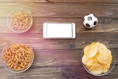 Soccer game. football fans. team sport. backgrounds texture of a tree. Smartphone with a white screen, chips, crackers, soccer ball on a wooden background stock photography