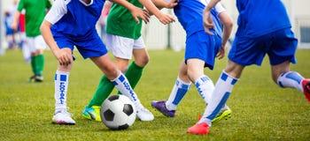 Soccer game for kids. Children kicking football ball Royalty Free Stock Images