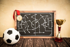 Soccer game strategy. Blackboard with drawn soccer game strategy. Ball, trophy and medal Royalty Free Stock Photography