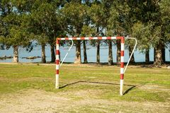 Soccer gate on amateur soccer court. With trees and sea at background stock images