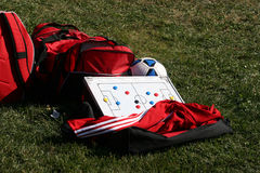 Soccer gear. Red duffel sport bag, jacket with soccer ball and tactic board Stock Image