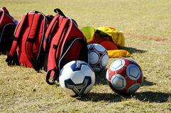 Soccer Gear. Soccer balls and bags on the sidelines at a youth soccer game royalty free stock photo