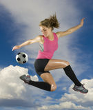 Soccer Girl. Girl Kicks soccer ball in mid air with clouds in background Royalty Free Stock Photo