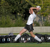 Soccer Girl varsity 5b. High School girl varsity soccer player passing the ball back into play from the side lines Stock Image